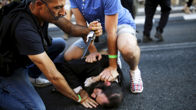 People disarm an Orthodox Jewish assailant after he stabbed and injured six participants at an annual gay pride parade in Jerusalem on Thursday, police and witnesses said July 30, 2015. REUTERS/Amir Cohen - RTX1MGFB